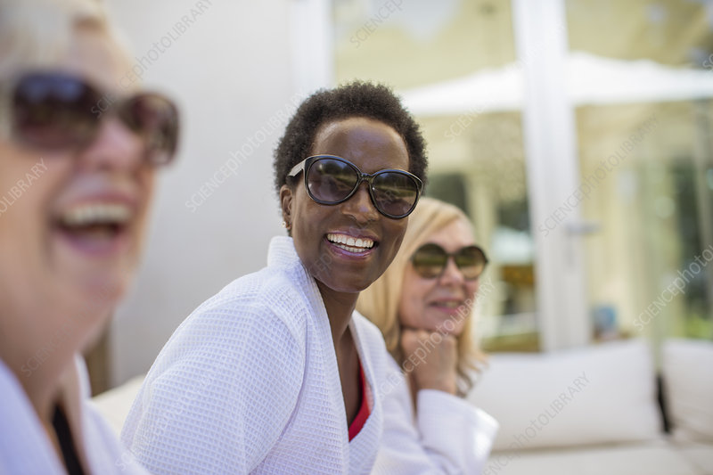 Senior women friends in spa bathrobes and sunglasses