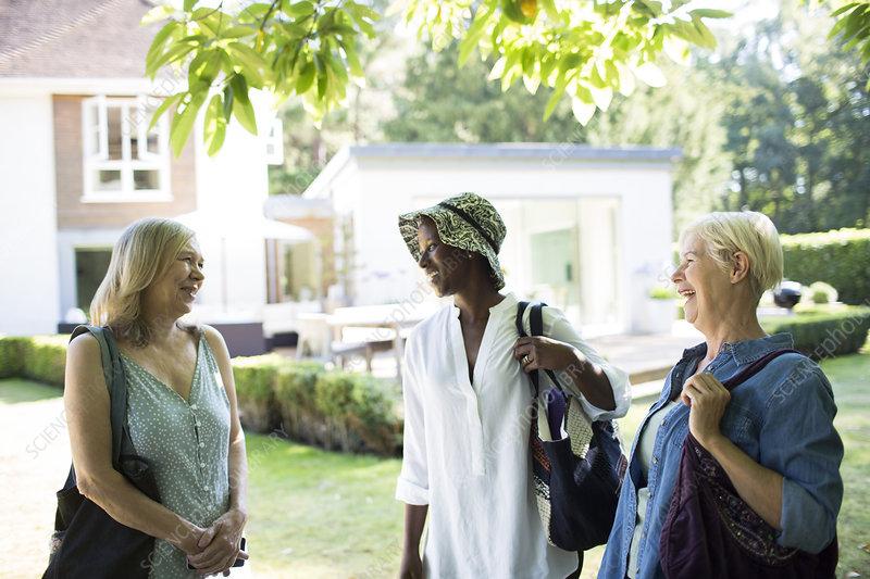 Happy senior women friends talking in summer garden