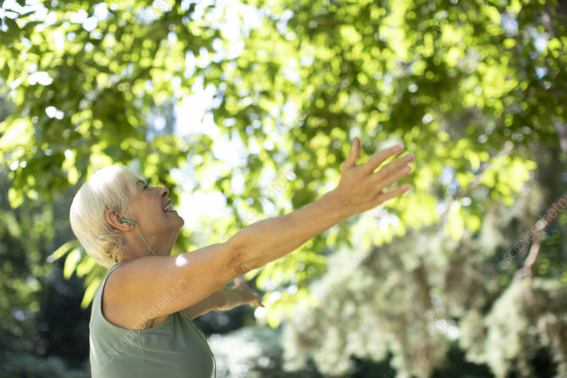 Senior woman with arms outstretched under summer trees