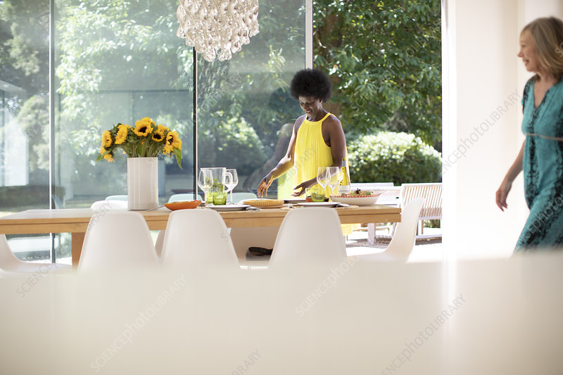 Mature woman in dress setting table for lunch