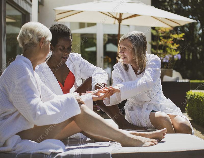 Senior women friends in spa bathrobes on hotel patio