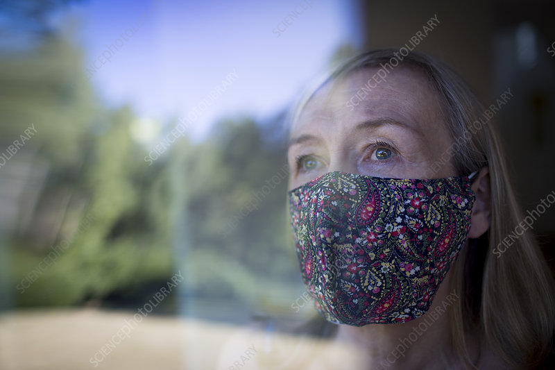 Worried senior woman in face mask at window