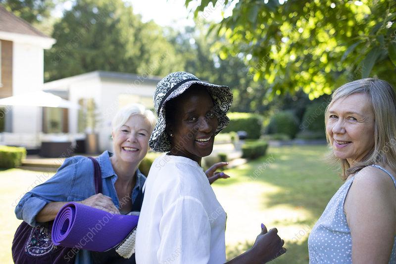 Portrait senior women with yoga mat in summer garden