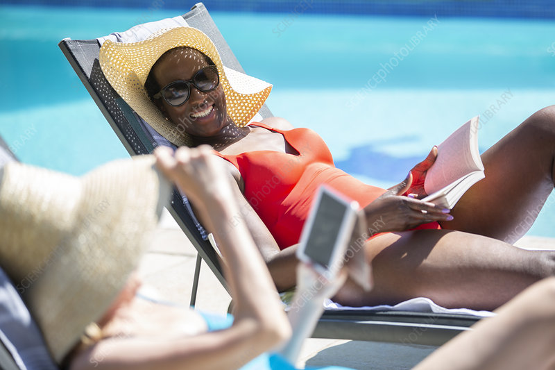 Senior women friends relaxing and sunbathing at poolside