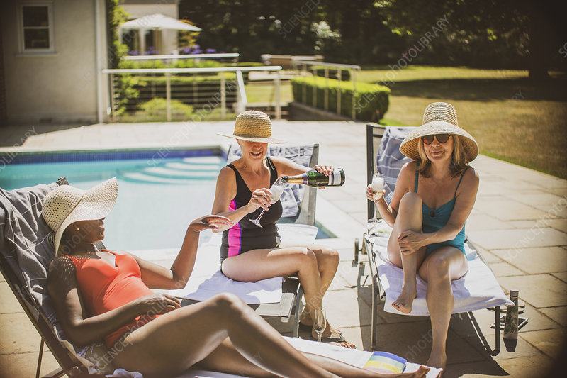 Senior women friends drinking champagne and sunbathing
