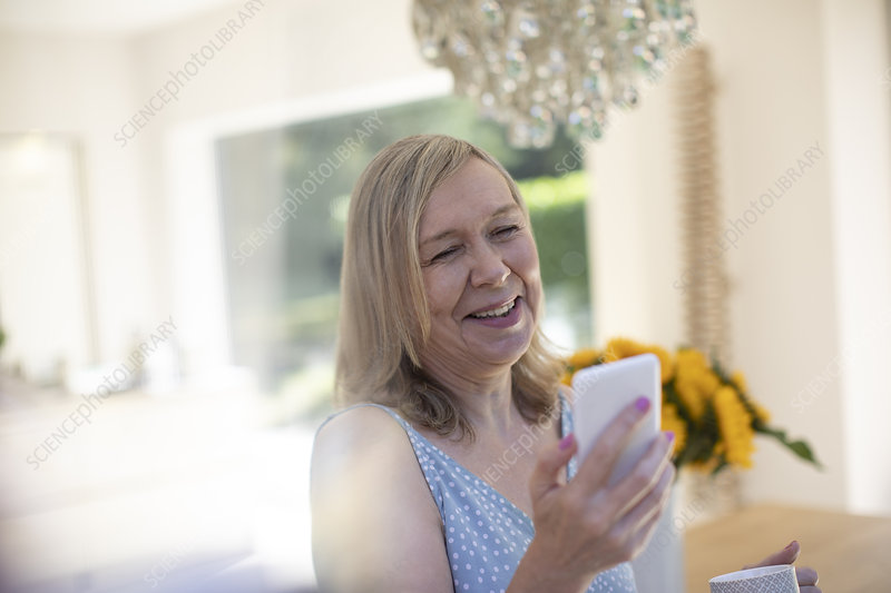 Smiling senior woman with smart phone at home
