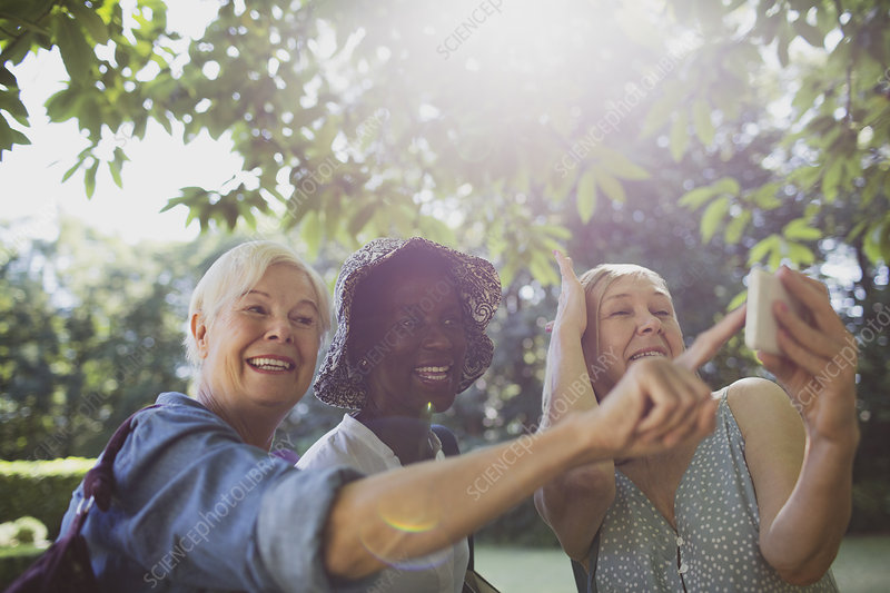 Playful senior women friends taking selfie in garden