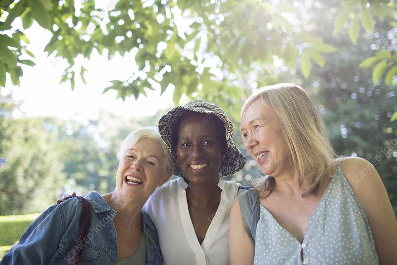 Portrait happy senior women in sunny summer garden