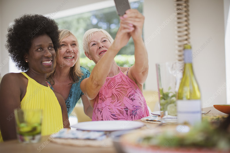 Senior women friends taking selfie at dining table