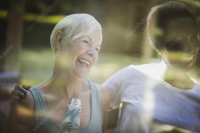 Happy senior women friends on sunny patio