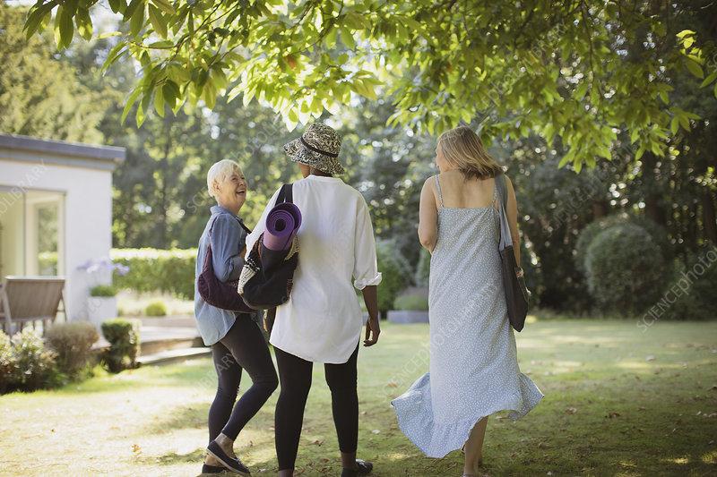 Happy senior women friends with yoga mat in garden
