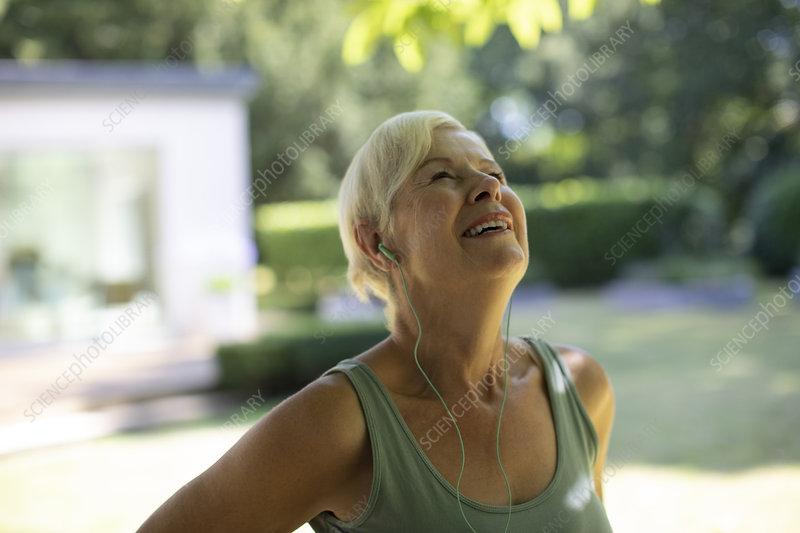 Happy senior woman with headphones exercising in garden