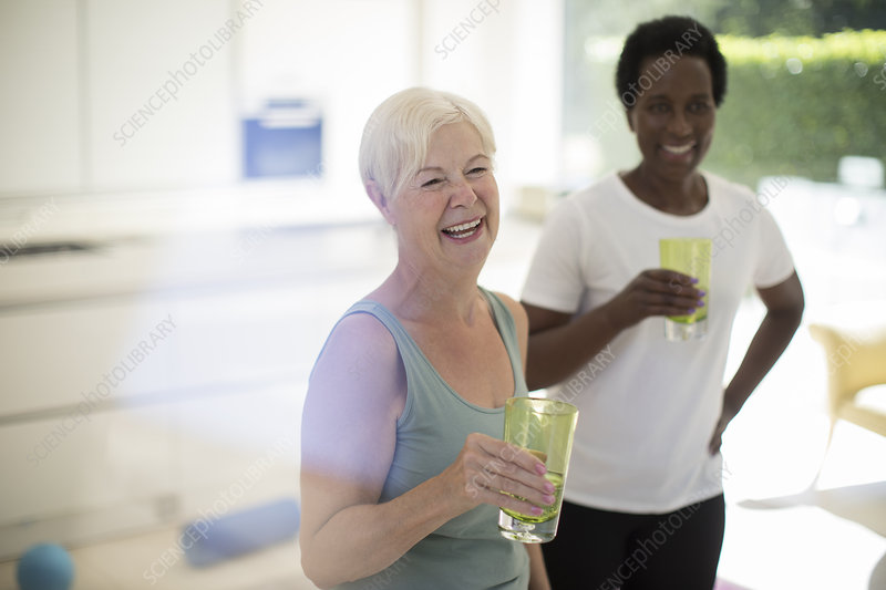 Senior women friends drinking water after workout at home