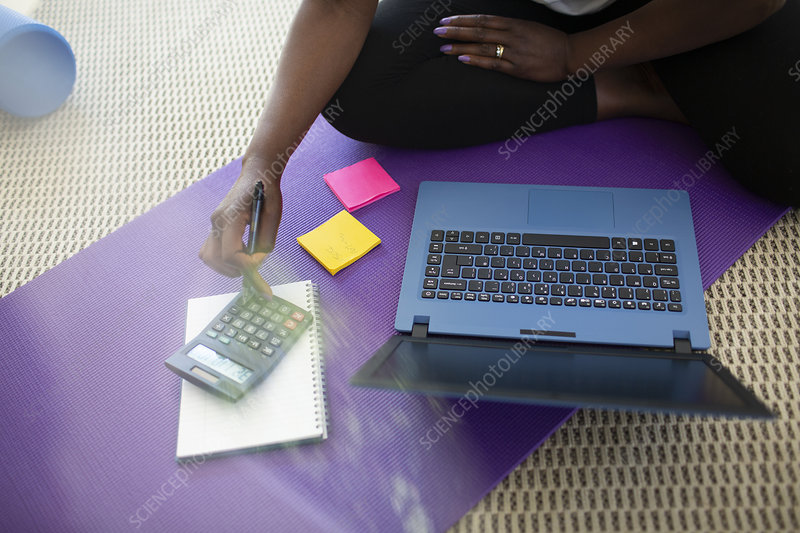 Woman paying bills at laptop on yoga mat at home