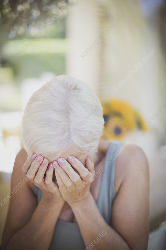 Stressed senior woman with head in hands