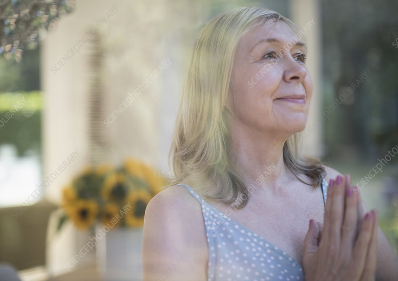 Serene senior woman meditating with hands clasped
