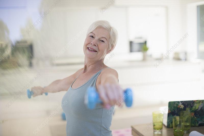 Portrait senior woman exercising with dumbbells