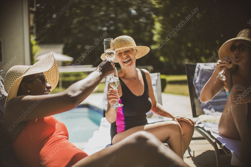 Senior women friends toasting champagne at poolside