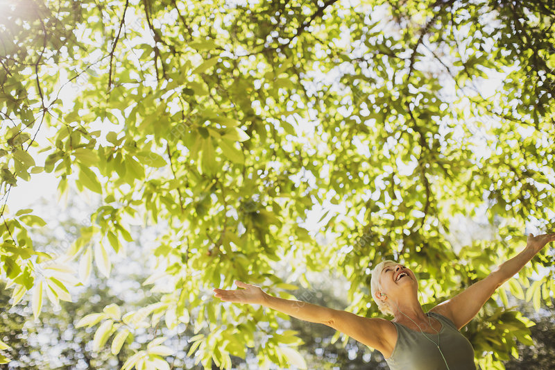 Exuberant senior woman with arms outstretched under tree