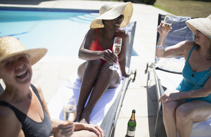 Senior women friends drinking champagne at summer poolside