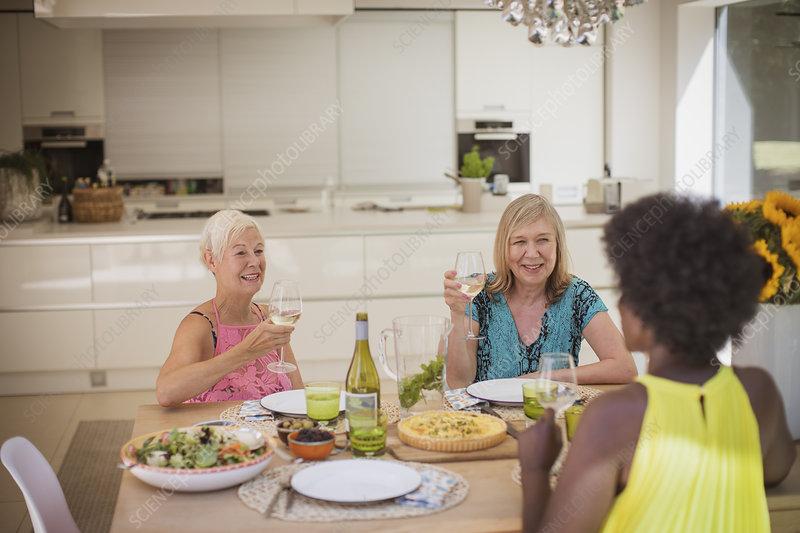 Senior women friends enjoying white wine with lunch