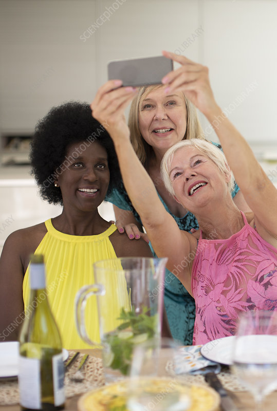 Happy senior women friends taking selfie at lunch