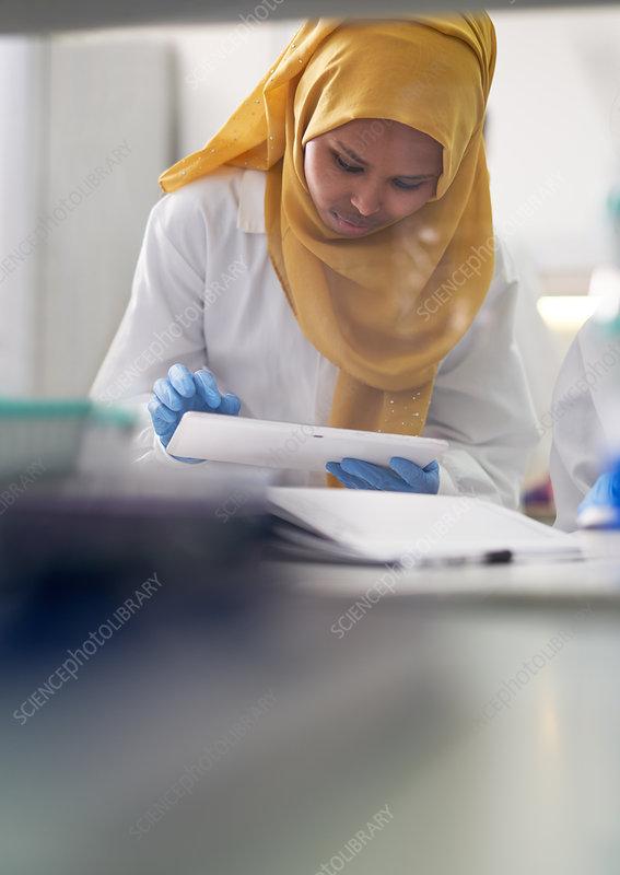Scientist in hijab using digital tablet
