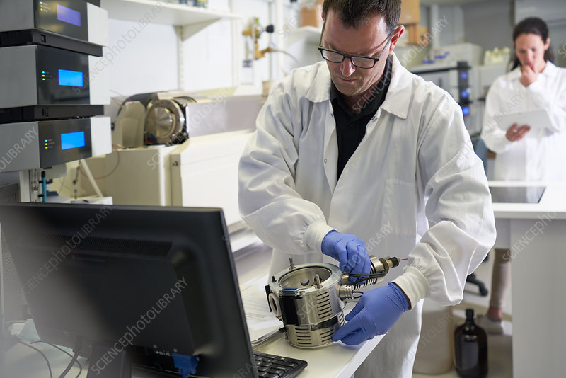 Male scientist using equipment at computer in laboratory