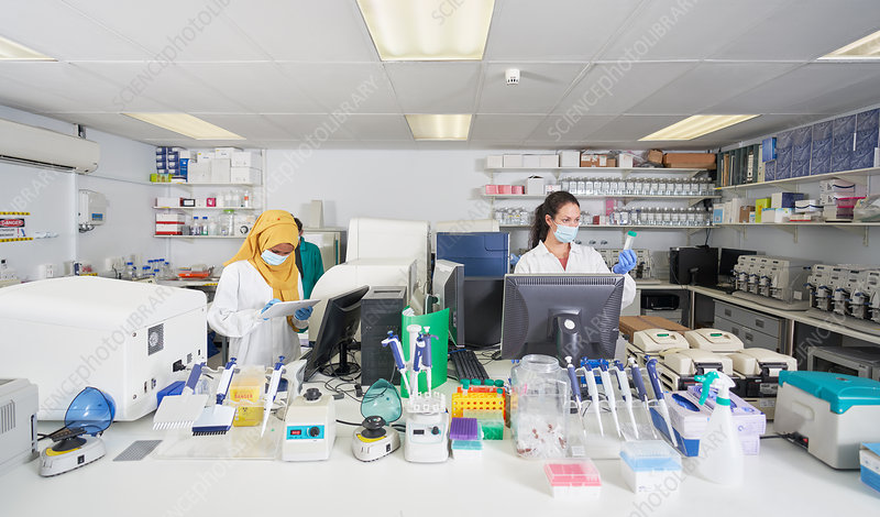 Female scientists in face masks working in laboratory