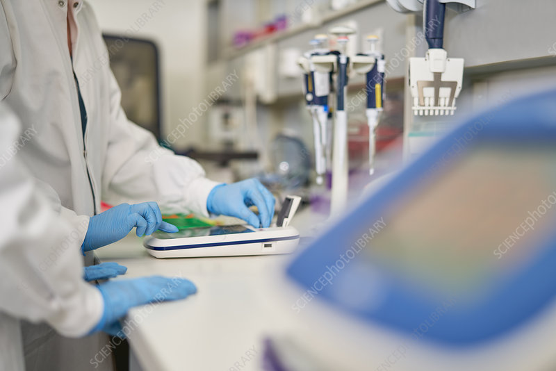 Scientists in rubber gloves using equipment in laboratory