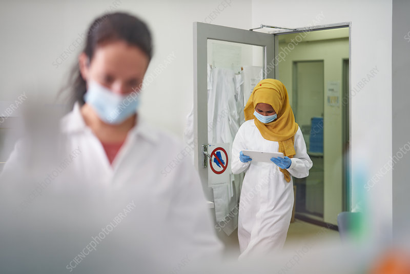 Scientist in face mask and hijab using digital tablet