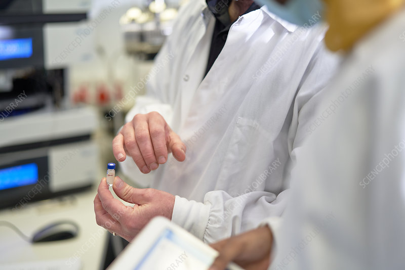 Close up scientists examining vial in laboratory