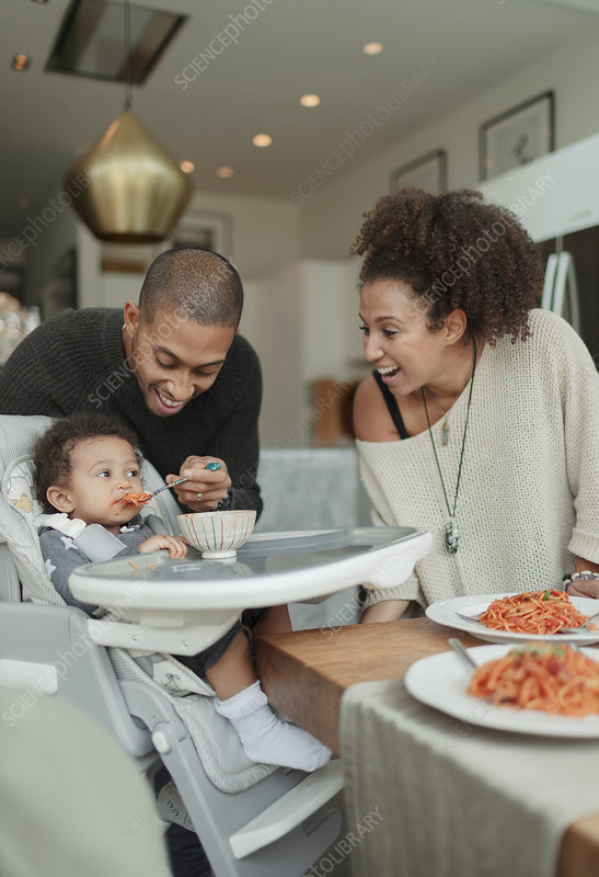 Happy couple feeding baby daughter in high chair