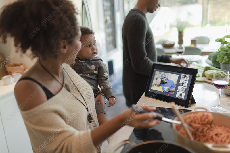 Family cooking dinner and video chatting by digital tablet