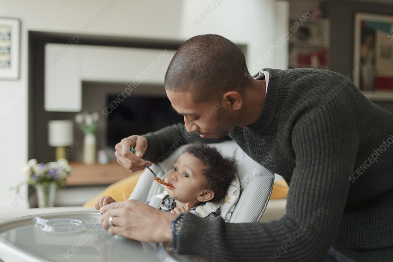 Father feeding baby daughter at high chair