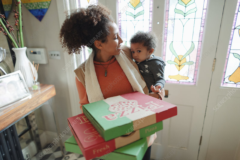 Mother with baby daughter receiving pizza delivery