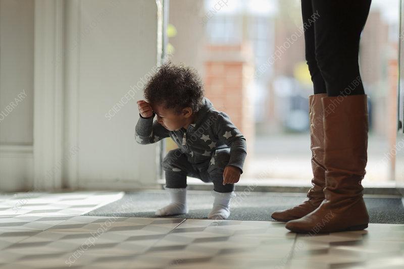 Cute baby girl in pyjamas crouching at front door