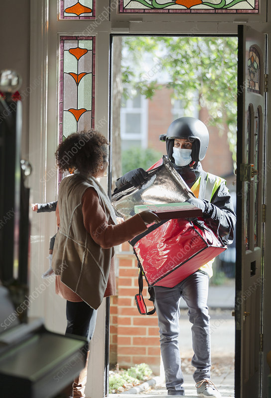 Woman receiving pizza from delivery man in face mask