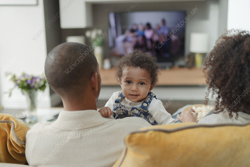 Portrait cute baby girl with parents on living room sofa