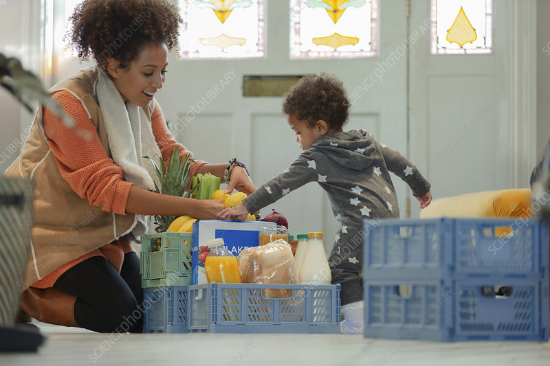 Baby daughter helping mother unload grocery delivery