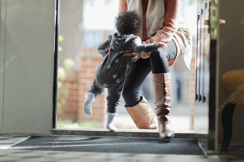 Mother lifting baby daughter in pyjamas at front door