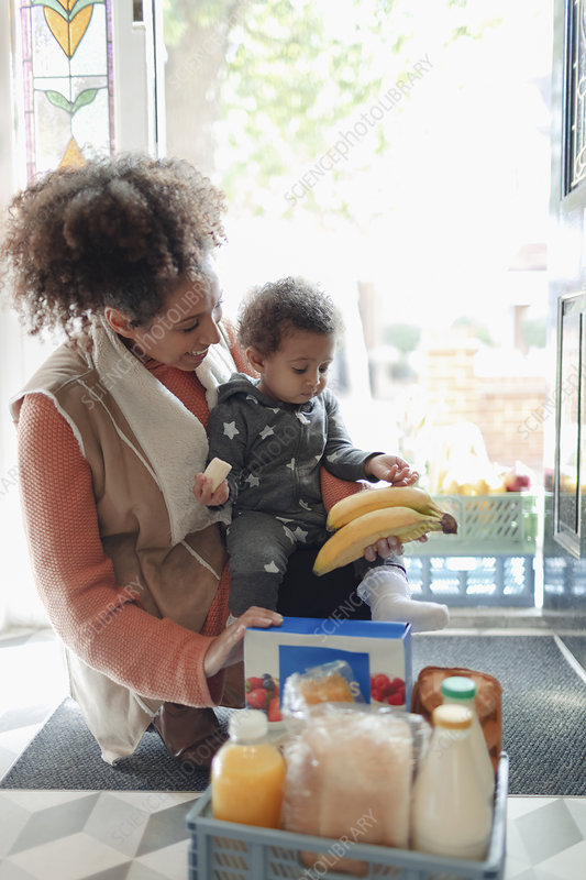 Mother and baby daughter receiving grocery delivery