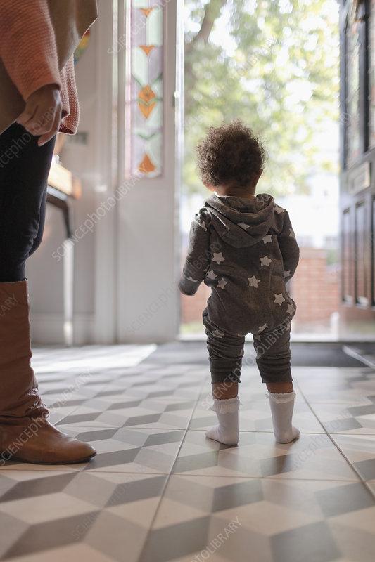 Baby girl in star pyjamas at front door