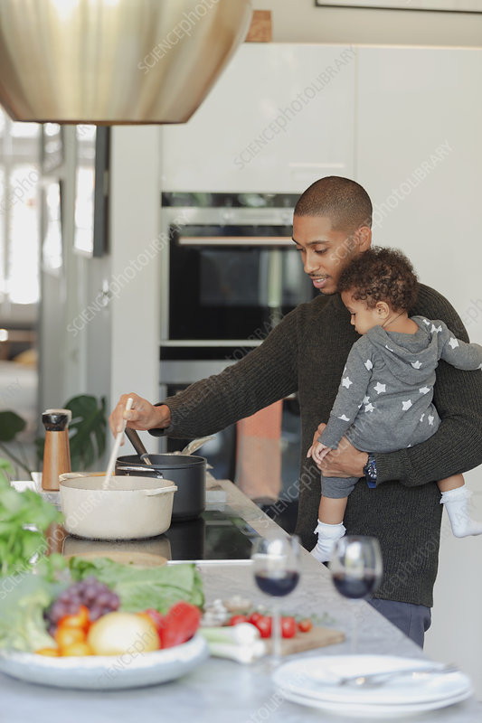 Father and baby daughter cooking at kitchen stove