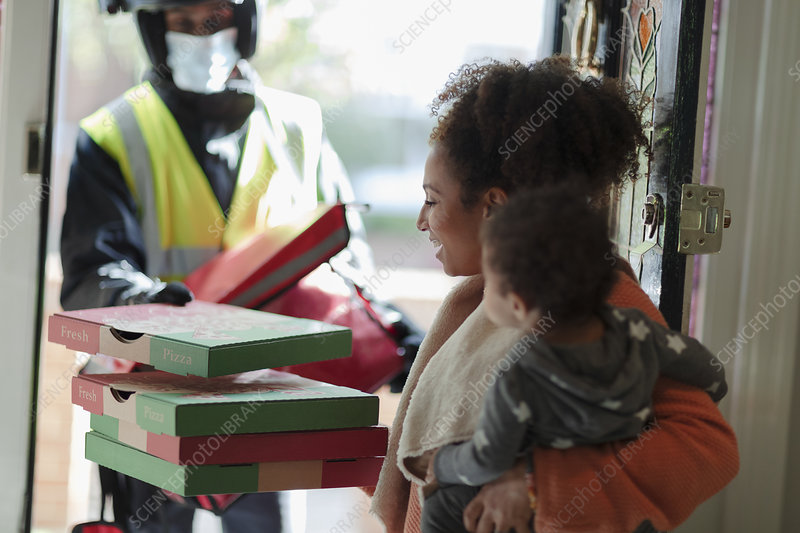 Mother with baby daughter receiving pizza