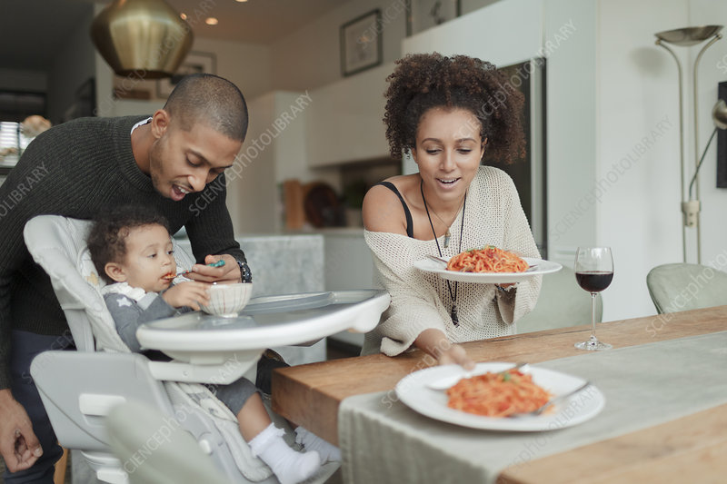Couple eating spaghetti and feeding baby daughter