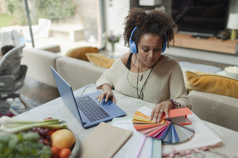 Female designer working from home at laptop