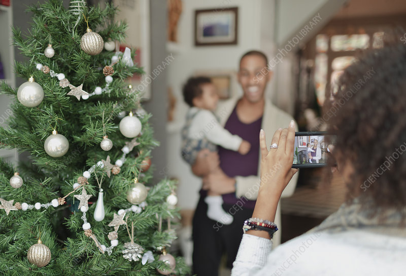 Woman photographing husband and baby daughter