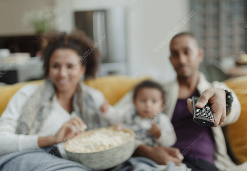 Family with remote control watching TV with popcorn