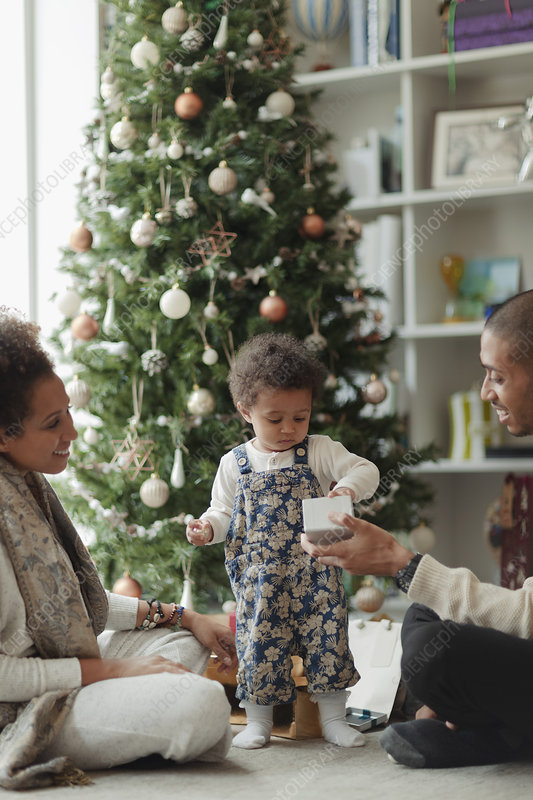 Couple helping baby daughter open Christmas gift